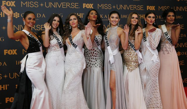 Miss Universe contestants blow kisses to photographers as they pose on the red carpet on the eve of their coronation Sunday, January 29, 2017, at the Mall of Asia in suburban Pasay city south of Manila, Philippines. Eighty-six conestants are vying for the title to succeed Pia Wurtzbach from the Philippines. From left, Chalita Suansane of Thailand, Dijana Cvijetic of Switzerland, Teodora Dan of Romania, Jihan Dimack of Tanzania, Cheryl Chou of Singapore, Zuzana Kollarova of Slovak Republic, Tansu Cakir of Turkey, Jayathi de Silva of Sri Lanka. (Photo by Bullit Marquez/AP Photo)