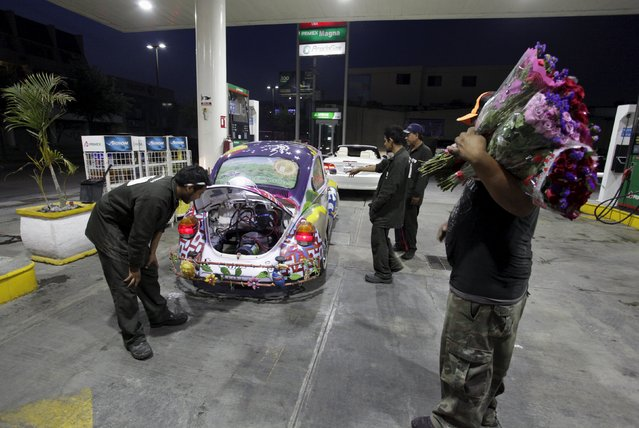 """Gas station attendants surround Rene Penia's VW Beetle 1995, locally called """"Vocho"""", in Monterrey April 22, 2015. (Photo by Daniel Becerril/Reuters)"""