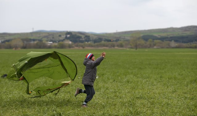 A migrant boy uses a piece of a tent as a kite as he runs in a field near a makeshift camp on the Greek-Macedonian border near the village of Idomeni, Greece March 10, 2016. (Photo by Stoyan Nenov/Reuters)