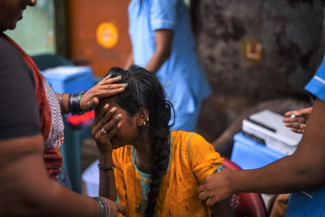 A woman reacts while receiving a dose of the COVID-19 vaccine at a slum during the fourth mega vaccination drive against the COVID-19 coronavirus disease, in Chennai, India, 03 October 2021. The Tamil Nadu state government organised the fourth mega COVID-19 vaccination drive to vaccinate more people across the state. So far, India has administered over 900 million cumulative COVID-19 vaccines, Union Minister for Health and Family Welfare Mansukh Mandaviya said on 02 October. (Photo by Idrees Mohammed/EPA/EFE)