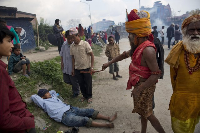A sadhu, or Hindu holy man, waves a string of beads to a man who broke down during a funeral of Saturday's earthquake victims on the banks of Bagmati river in Kathmandu, Nepal, Sunday, April 26, 2015. (Photo by Bernat Armangue/AP Photo)