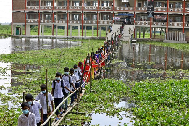 Students leave school via a bamboo bridge after the area was hit by floods in Gazipur, Bangladesh on September 12, 2021. (Photo by Harun-Or-Rashid/Eyepix Group/Rex Features/Shutterstock)