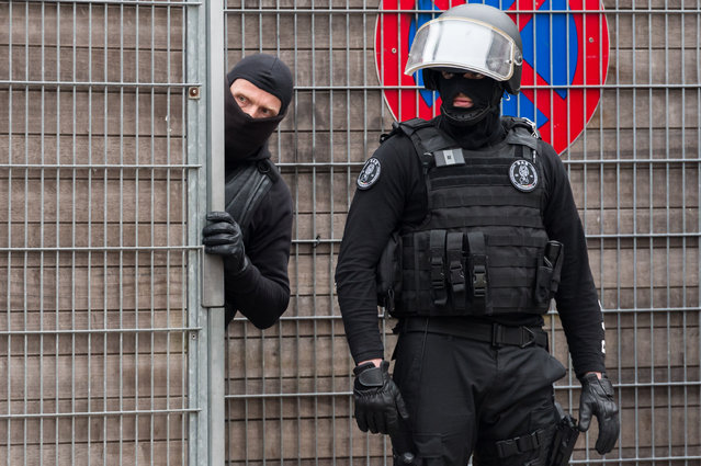Police officers guard an entrance of a school during a raid in the Molenbeek neighborhood of Brussels, Belgium, Friday March 18, 2016. Police have descended in force to search a residence in the Molenbeek, and Belgian media reported gunshots had been fired. RTBF French-language TV reported late Friday afternoon that two people had been wounded, and that one might be Paris attacks fugitive Salah Abdeslam. (Photo by Geert Vanden Wijngaert/AP Photo)