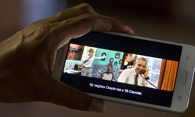 """A woman poses for a photo, holding her cell phone that shows a frame from the video released by the White House of President Barack Obama joking with Cuban comedian Panfilo, in Havana, Cuba, Saturday, March 19, 2016. The video released Saturday shows Panfilo calling the White House to find out the weather for a baseball game during Obama's trip to Cuba. Obama answers and banters with Panfilo, using Cuban slang to say """"Panfilo! Get outta here! What's going on?"""" (Photo by Ramon Espinosa/AP Photo)"""