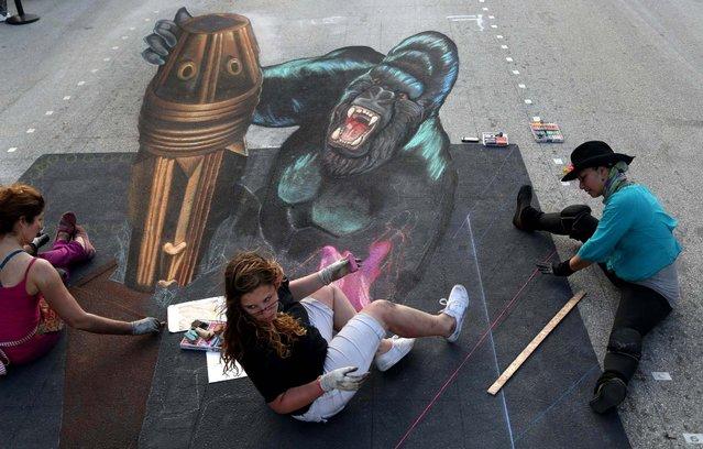 Tracy Lee Stum, of Ventura, CA., left, Alex Alfeo, 16, of Boynton Beach, and Sharyn Namnath, of Santa Barbara, CA., work on King Kong. (Photo by Greg Lovett/The Palm Beach Post)