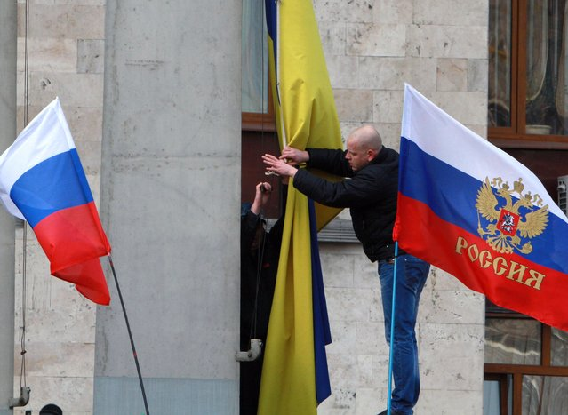 Pro-Russian activists remove the Ukrainian flag, center, to replace it with a Russian one on an administration office in the center of Donetsk, Ukraine, Saturday, March 1, 2014. (Photo by Sergey Vaganov/AP Photo)