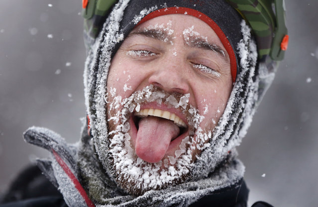 Cyclist David Cassidy of Bangor, Maine, enjoys the moment after crossing the finish line in an 18-mile bike race at the Fat Tire Festival at the Sugarloaf ski resort, Saturday, February 11, 2017, in Carrabassett Valley, Maine. Riders had to endure heavy snowfall and 2 degree F temperatures as parts of New England get hit with another winter storm. (Photo by Robert F. Bukaty/AP Photo)