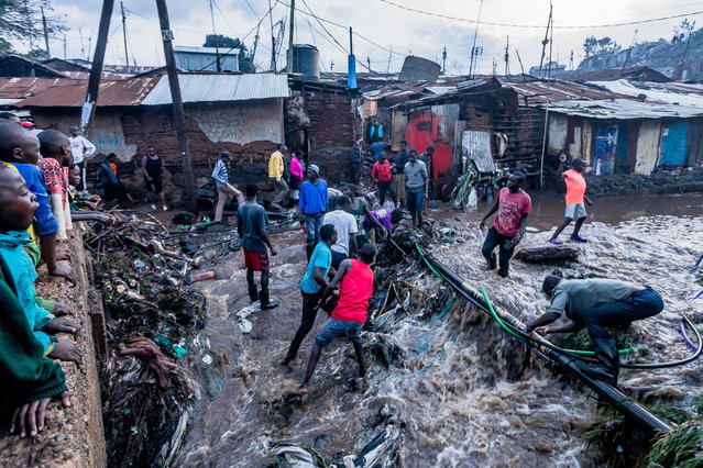People remove debris from water hoses which deliver clean water after the rain at Kibera slum in Nairobi, on April 23, 2019. (Photo by Brian Otieno/AFP Photo)
