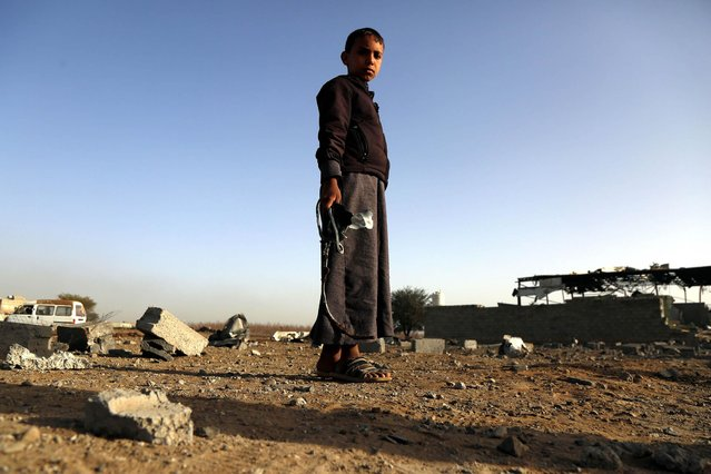 A Yemeni child holds missile shrapnel outside a factory after it destroyed in airstrikes carried out by warplanes of the Saudi-led coalition killing three civilians and injured six others on January 20, 2019 in Sana'a, Yemen. (Photo by Mohammed Hamoud/Getty Images)