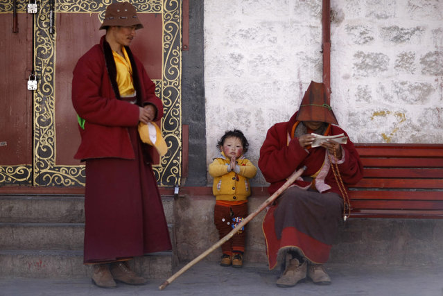 A boy puts his palms together as he rests with his family outside Jokhang Monastery in Lhasa, Tibet autonomous region, March 4, 2014. Picture taken  March 4, 2014. (Photo by Jacky Chen/Reuters)