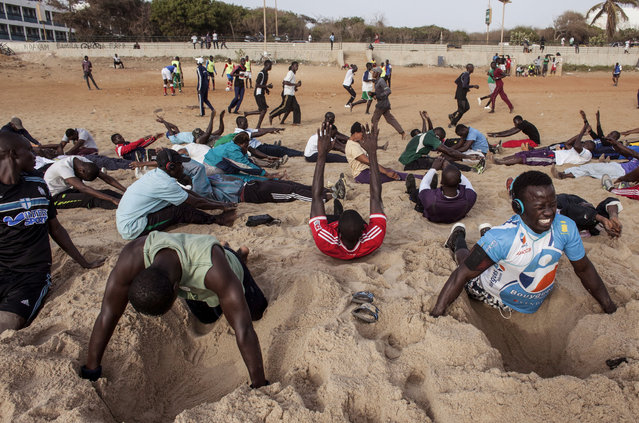 In this photo taken on Tuesday, May 7, 2015, people take part in different type of sport moves, including push ups over dug out holes in the sand at Fann Beach in Dakar, Senegal. It isn't Venice Beach, it's Fann Beach, and the sounds of waves serves as a background rhythm for hundreds of super-fit, sport loving Senegalese who swarm to the beach en masse every day for a workout to chants and cheers. (Photo by Jane Hahn/AP Photo)
