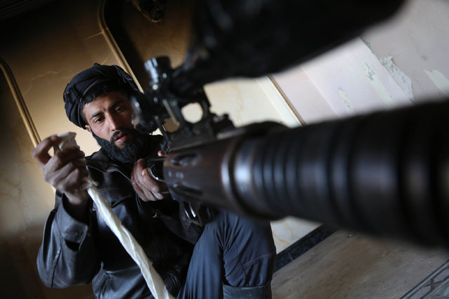 A fighter from Jaish al-Islam (Islam Army) prepares a Russian-made sniper rifle in the rebel-held area of Harasta, on the northeastern outskirts of the capital Damascus, on February 21, 2017. (Photo by Amer Almohibany/AFP Photo)