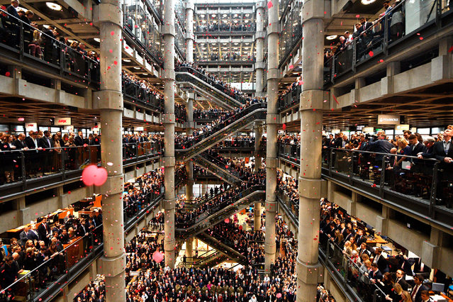 Staff line the atrium as poppies fall during an Armistice commemoration service at Lloyd's of London on 9 November 2018. (Photo by Neil Hall/EPA/EFE)
