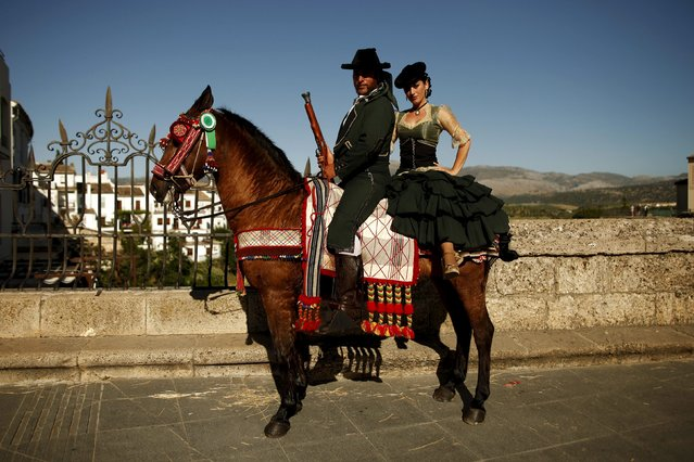 "Francisco Javier Moreno (L), 35, and his wife Maria Auxiliadora Canca, 34, dressed as bandits pose for a photo with their horse as they participate in the third edition of ""Ronda Romantica"" (Romantic Ronda) in Ronda, southern Spain, May 16, 2015. (Photo by Jon Nazca/Reuters)"