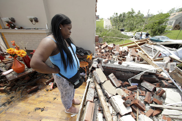 Iesha McClain looks through her destroyed home Thursday, May 23, 2019 after a tornado tore though Jefferson City, Mo. late Wednesday. (Photo by Charlie Riedel/AP Photo)