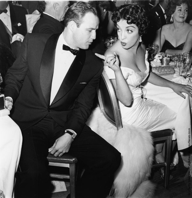 American actor Marlon Brando turns to face Mexican actor Katy Jurado, who gestures at him during a formal awards dinner, 1950s