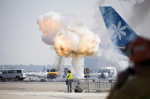 Pyrotechnic explosions goes off near a parked airplane during a disaster drill at Los Angeles International Airport (LAX) in Los Angeles, California, USA, 13 April 2016. A full-scale simulated aircraft crash landing was conducted to test the city and airport's emergency response systems. (Photo by Eugene Garcia/EPA)
