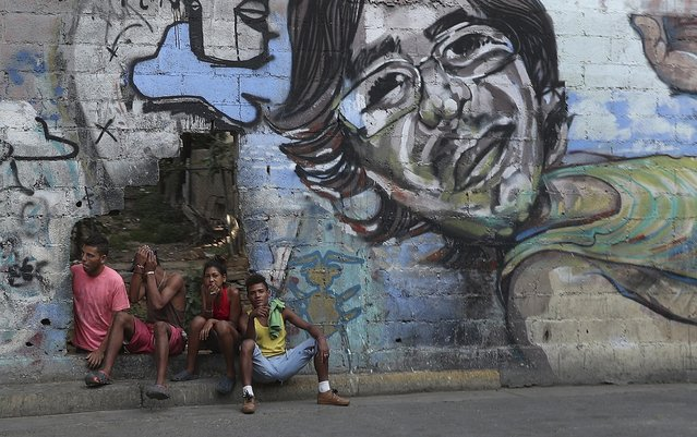 A group of young people rest in a hole in the wall at the Agua Salud neighborhood of Caracas, Venezuela, Wednesday, May 15, 2019. More than 3 million Venezuelans have left their homeland in recent years amid skyrocketing inflation and shortages of food and medicine. U.S. administration officials have warned that 2 million more are expected to flee by the end of the year if the crisis continues in the oil-rich nation. (Photo by Martin Mejia/AP Photo)