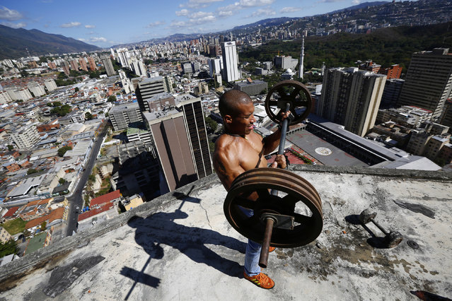 """Gabriel Rivas, 30, lifts weights on a balcony on the 28th floor of the """"Tower of David"""" skyscraper in Caracas February 9, 2014. (Photo by Jorge Silva/Reuters)"""