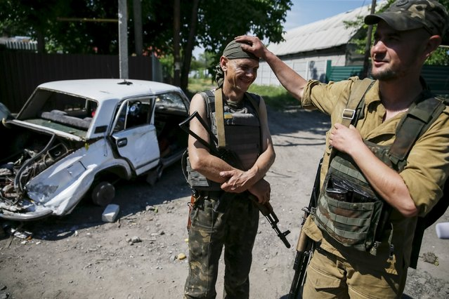 """Members of the Ukrainian armed forces are seen in the town of Maryinka, eastern Ukraine, June 5, 2015. Ukraine's president told his military on Thursday to prepare for a possible """"full-scale invasion"""" by Russia all along their joint border, a day after the worst fighting with Russian-backed separatists in months.  REUTERS/Gleb Garanich"""