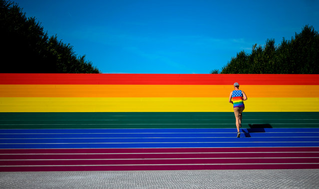 A man walks on steps covered in rainbow colors for Pride Month at Franklin D. Roosevelt Four Freedoms Park on June 15, 2019 in New York City. Organizers claim it is the largest LGBT pride flag in New York City and measures around 12 by 100 feet (3.6 x 30 meters). (Photo by Johannes Eisele/AFP Photo)