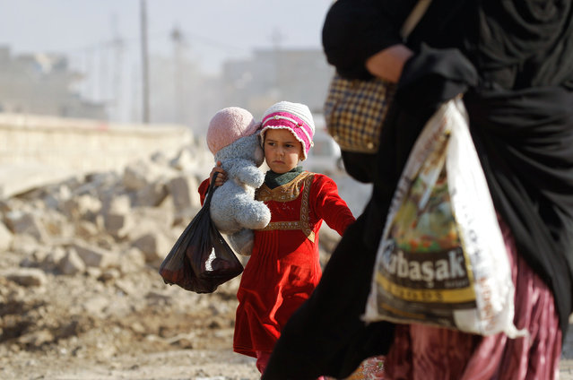 A displaced Iraqi girl carries her doll as she flees her home while Iraqi forces battle with Islamic State militants, in western Mosul, Iraq March 7, 2017. (Photo by Zohra Bensemra/Reuters)