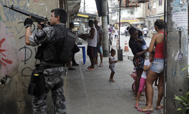 A police officer takes up position during an operation at the Mare slums complex in Rio de Janeiro March 25, 2014. (Photo by Ricardo Moraes/Reuters)