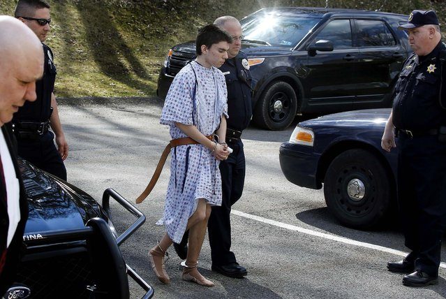 Alex Hribal, the suspect in the multiple stabbings at Franklin Regional High School, is escorted by police to a district magistrate to be arraigned in Export, Pa., on April 9, 2014. Authorities say Hribal has been charged after allegedly stabbing and slashing at least 19 people including students in the crowded halls of his suburban Pittsburgh high school. (Photo by Keith Srakocic/Associated Press)