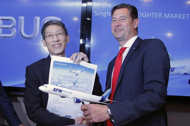 Chief Financial officer of Airbus Group Harald Wilhelm, right and Serh Ghee Lim President of ST Aerospace pose after the agreement signature during an Airbus press conference at the Paris Air Show, in Le Bourget airport, north of Paris, Wednesday, June 17, 2015. Airbus has signed an agreement with Singapore based ST Aerospace to offer passenger-to freighter conversion solutions for its A320/A321aircraft. (AP Photo/Francois Mori)