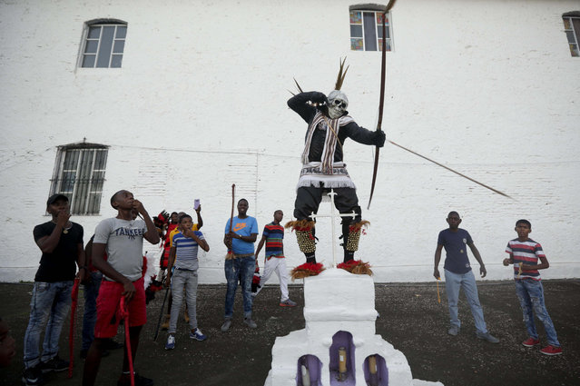 """In this March 18, 2017 photo, a man dressed as a """"devil"""" performs near the San Felipe church during the Congos and Devils festival in Portobelo, Panama. The biennial festival takes place in the historical town along the Atlantic Panamanian coast. The Portobelo festival, a blend of Catholic and African beliefs, was established in 1999 by the community to preserve their culture in honor of their ancestors, who were escaped former slaves from the Congo known as """"Cimarrons"""". (Photo by Arnulfo Franco/AP Photo)"""
