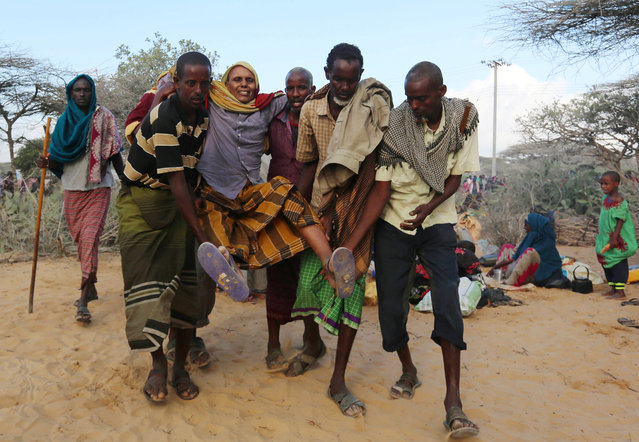 Internally displaced Somali people carry a man with a broken leg as they flee from drought stricken regions in Lower Shabelle region before entering makeshift camps in Mogadishu on March 17, 2017. (Photo by Feisal Omar/Reuters)