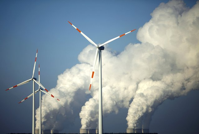 Steam billows from the cooling towers of Vattenfall's Jaenschwalde brown coal power station behind wind turbines near Cottbus, eastern Germany, in this December 2, 2009 file photo. Germany agreed on July 2, 2015 to mothball about five of the country's largest brown coal power plants to meet its climate goals by 2020, after months of wrangling between the parties in Chancellor Angela Merkel's coalition. (Photo by Pawel Kopczynski/Reuters)