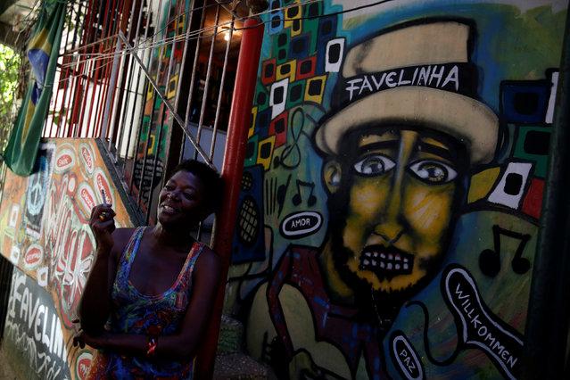 Solange, a worker at Pousada Favelinha (Little favela) hostel, stands near an entrance, in Pereira da Silva favela in Rio de Janeiro, Brazil, April 21, 2016. (Photo by Pilar Olivares/Reuters)