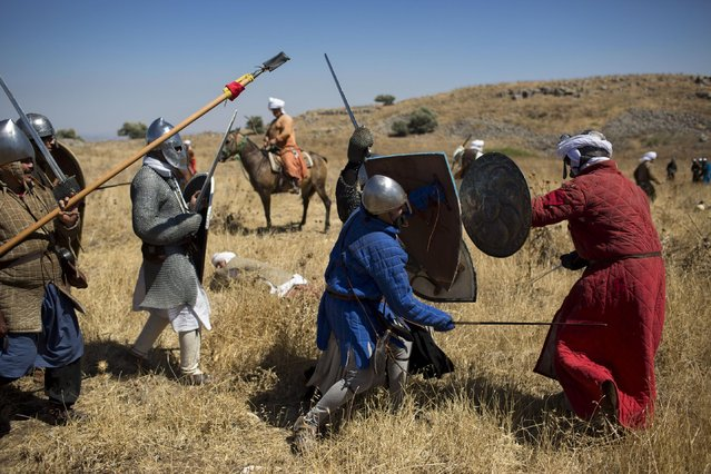 In this Saturday, July 4, 2015 photo, Israeli and Russian members of knight clubs participate in the reenactment of the Battle of Hattin in Horns of Hattin, northern Israel. (Photo by Oded Balilty/AP Photo)