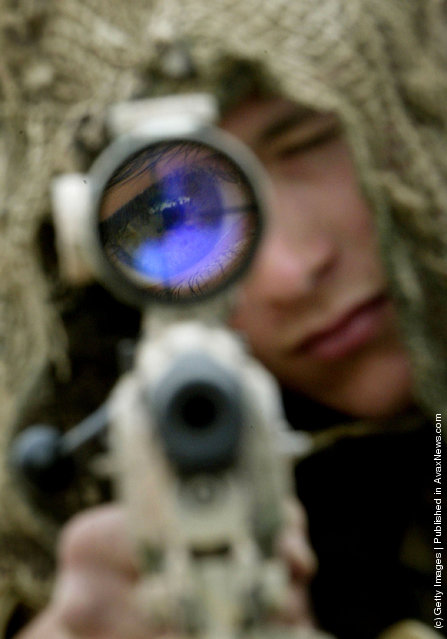 A British soldier from 3 Commando Brigade looks through the sight of his sniper rifle at Camp Gibraltar