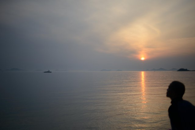 The sun sets over Jindo harbour on April 23, 2014. The confirmed death toll from South Korea's ferry disaster crossed 100 on April 22, as dive teams, under growing pressure from bereaved relatives, accelerated the grim task of recovering hundreds more bodies from the submerged vessel. (Photo by Ed Jones/AFP Photo)