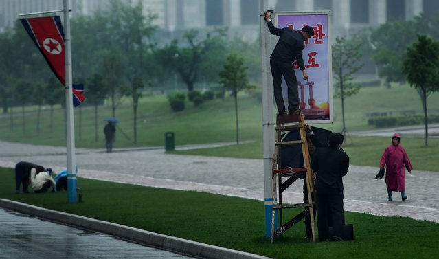 Workers repair a Workers' Party poster as the Party's seventh congress gets underway today in Pyongyang, North Korea on May 6, 2016. Leader Kim Jong Un is expected to speak.Other grand and patriotic festivities are also on tap. (Photo by Linda Davidson/The Washington Post)