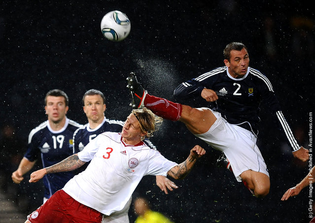 Phil Bardsley of Scotland clears the ball under pressure from Simon Kjaer of Denmark during the International Friendly Match between Scotland and Denmark at Hampden Park
