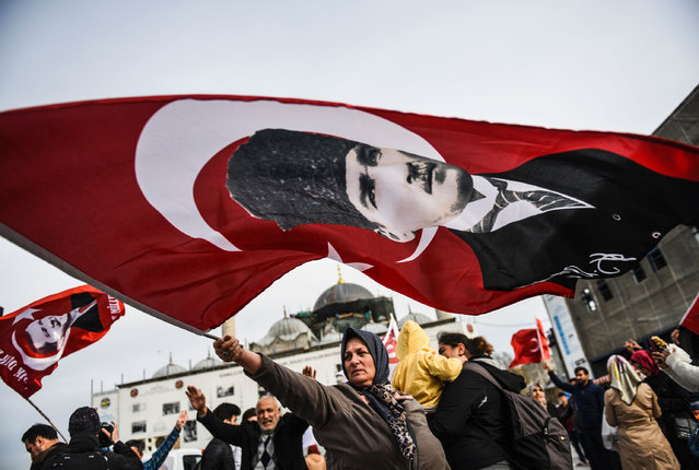 """A Turkish woman  supporting the """"No"""" vote in the upcoming constitutional referendum campaign waves a Turkish flag with a picture of modern Turkey's founder Mustafa Kemal Ataturk in front of Yeni Camii on April 12, 2017  during a campaign rally for the """"Yes""""  in Istanbul's Eminonu district. The Turkish public will vote on April 16, 2017 on whether to change the current parliamentary system into an executive presidency. (Photo by Bulent Kilic/AFP Photo)"""