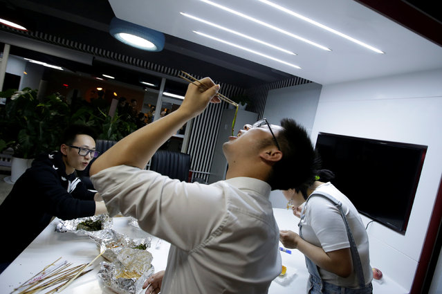 Yu Xiaojian, an employee at Goopal Group, eats with his colleagues during a break at work around midnight, in Beijing, China, April 19, 2016. (Photo by Jason Lee/Reuters)