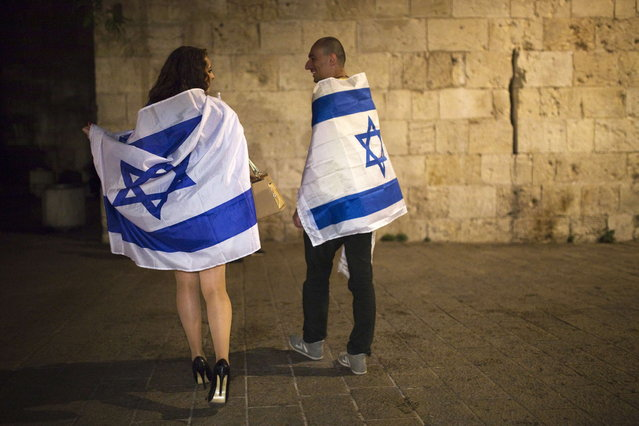 Israelis covered with Israel's national flags walk outside the Jerusalem old city walls during celebrations marking Israel's 66th Independence Day in Jerusalem May 5, 2014. (Photo by Amir Cohen/Reuters)