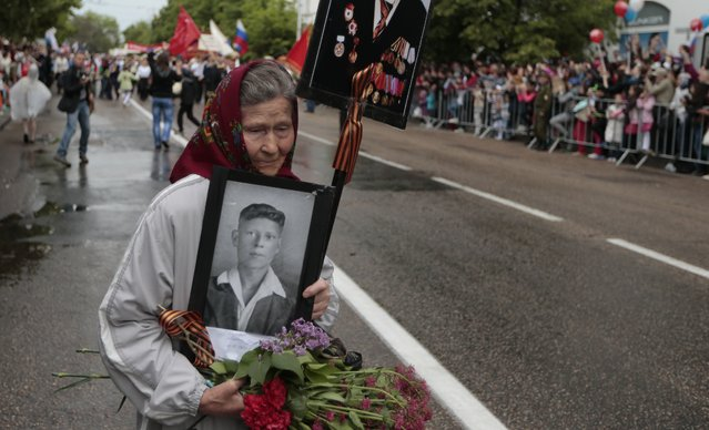 A woman holds a portrait of her relative who served in the Soviet Army in WWII, during a Victory Day military parade in Sevastopol, Crimea, Friday, May 9, 2014. Crimea, which hosts a major Russian Black Sea Fleet base, is also set to hold a massive navy parade in the port of Sevastopol, celebrating the Russian takeover. (Photo by Ivan Sekretarev/AP Photo)