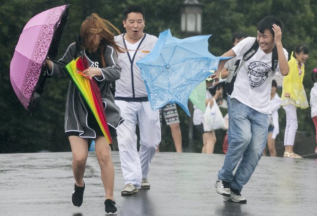 Tourists hold umbrellas as they tour the West Lake against strong wind under the influence of Typhoon Chan-hom, in Hangzhou, Zhejiang province, China, July 11, 2015. One of the most powerful typhoons to strike eastern China in decades disrupted air, rail and sea transport on Saturday after forcing the evacuation of more than a million people from the provinces of Zhejiang and Jiangsu, state media reported. (Photo by Reuters/Stringer)