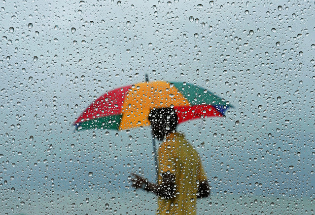 A man carrying an umbrella is seen through a window covered with rain drops during a wet day in Colombo, Sri Lanka on September 24, 2019. (Photo by Dinuka Liyanawatte/Reuters)