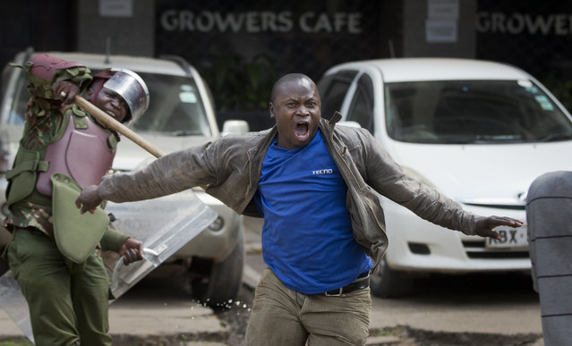 An opposition supporter yells out as he is beaten with a wooden club by riot police while trying to flee, during a protest in downtown Nairobi, Kenya Monday, May 16, 2016. (Photo by Ben Curtis/AP Photo)