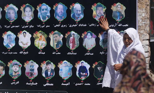 An Afghan woman cries as she touches a banner displaying photographs of victims of the Dubai City wedding hall bombing during a memorial service in Kabul, Afghanistan, Tuesday, August 20, 2019. The deadly bombing at a wedding in Afghanistan's capital late last Saturday that killed dozens of people was a stark reminder that the war-weary country faces daily threats not only from the long-established Taliban but also from a brutal local affiliate of the Islamic State group, which claimed responsibility for the attack. (Photo by Rafiq Maqbool/AP Photo)