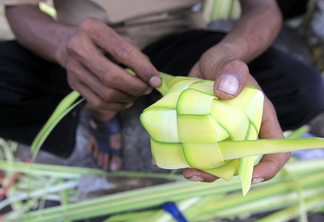 """An Indonesian man makes """"ketupat"""", traditional rice cooked in coconut leaf casings at a local market in Jakarta, Indonesia, 15 July 2015. Muslims around the world are preparing for Eid Al-Fitr expected to fall this week, marking the end of Ramadhan. (Photo by Bagus Indahono/EPA)"""