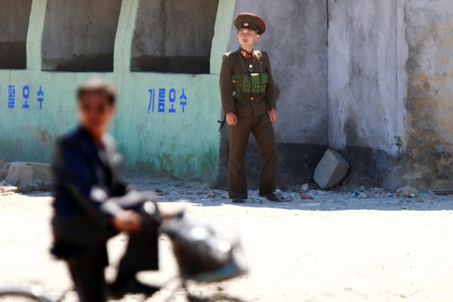 A man cycles past a North Korean soldier in Sinuiju, North Korea, September 2018. (Photo by Jacky Chen/Reuters)