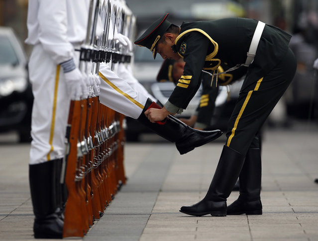 Members of an honour guard clean their boots as they get ready for a welcoming ceremony for the visiting Portugal's President Anibal Cavaco Silva (not seen), outside the Great Hall of the People in Beijing, May 15, 2014. (Photo by Kim Kyung-Hoon/Reuters)