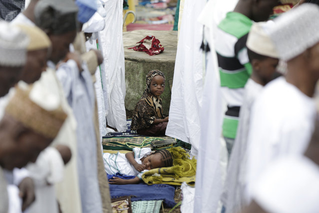 A girl watches as Nigeria Muslims attend Eid al-Fitr prayer, in Lagos, Nigeria, Friday, July 17, 2015, marking the end of the Muslim holy fasting month of Ramadan. (Photo by Sunday Alamba/AP Photo)